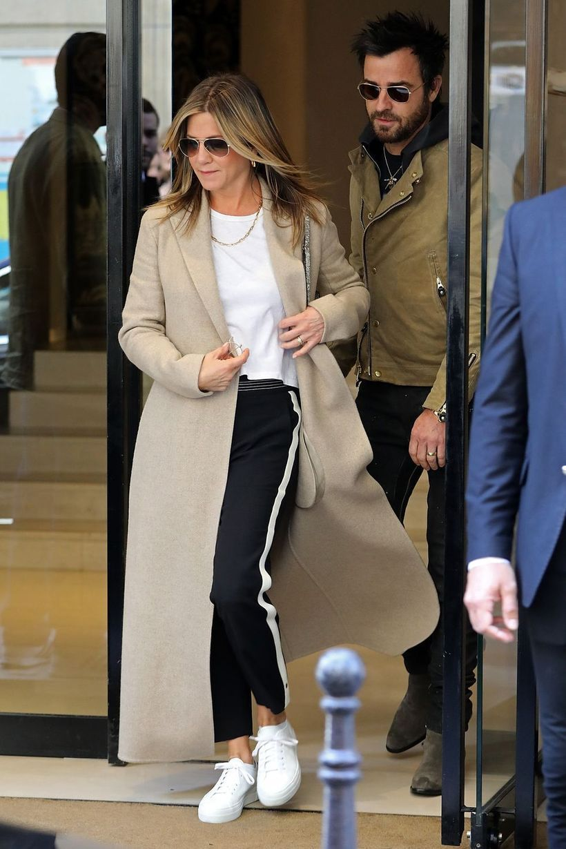 Long brown outer with white t-shirt, black pants and white shoes