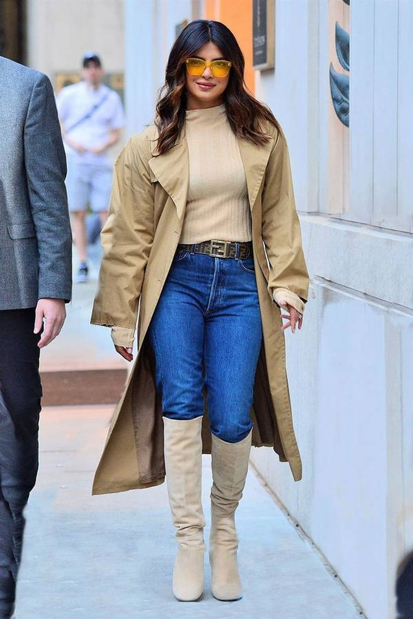 Long brown outer with beige t-shirt, blue pants and beige boots